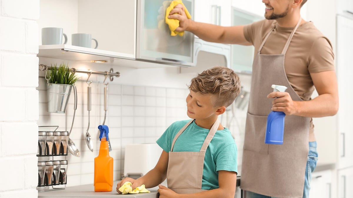 A dad and son cleaning the kitchen to help out with chores.