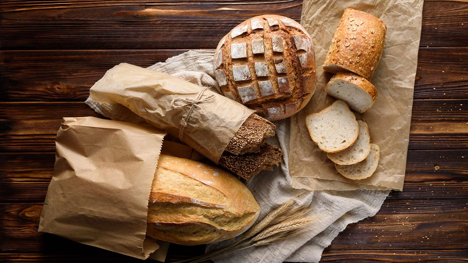 Four kinds of artisan bread, wrapped in or sitting on top of paper bags.