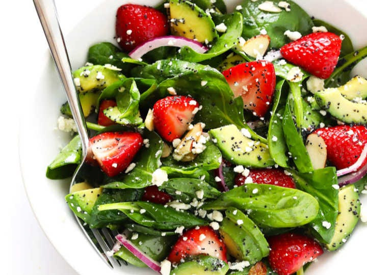 A gorgeous crisp spring salad filled with spinach, avocado, strawberries, red onion and poppy seed dressing.