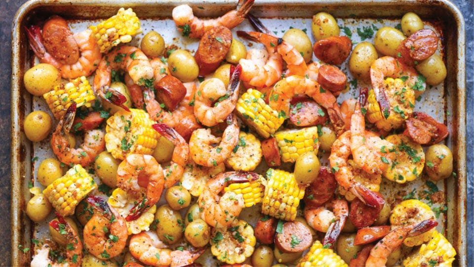 A shrimp boil dinner consisting of corn, potatoes, shrimp and andouille sausage all scattered on a sheet pan.