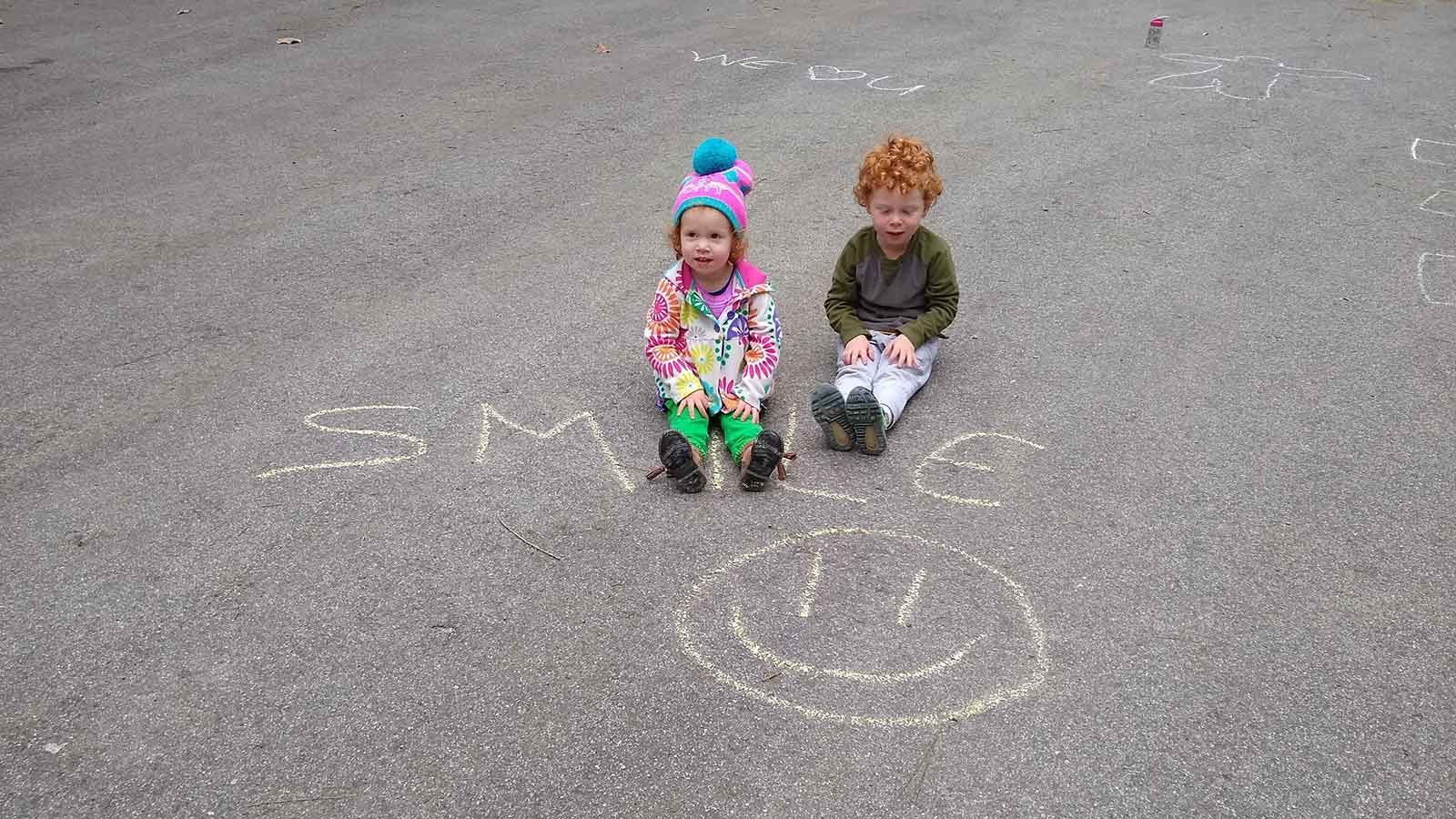 A little girl and boy sitting on the pavement next to some chalk drawings.