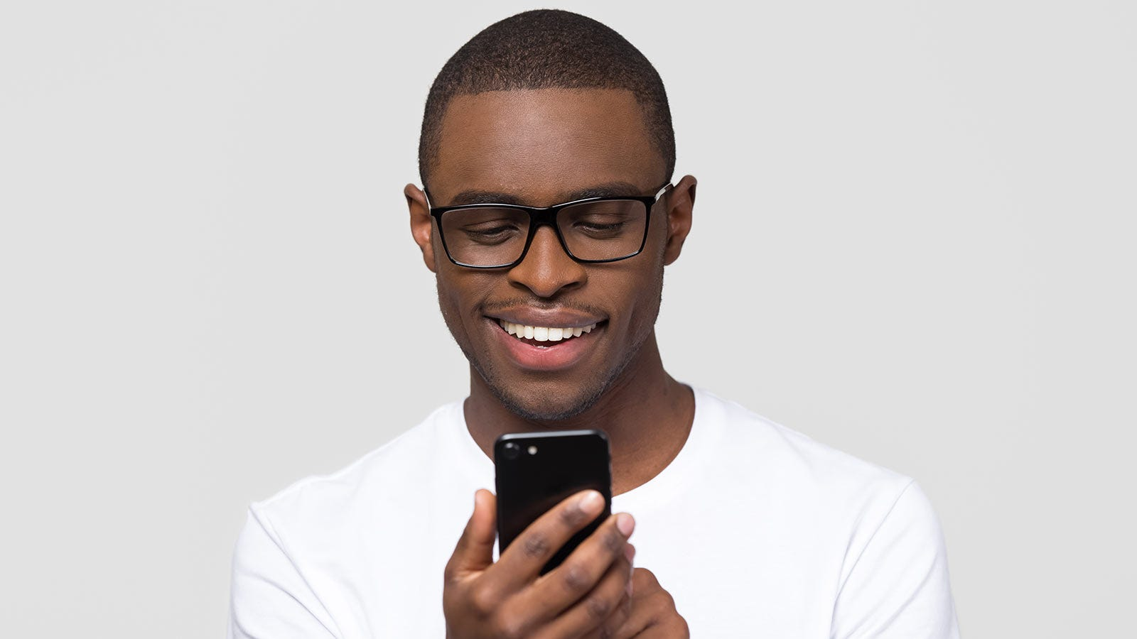 A man looking at his phone and smiling.