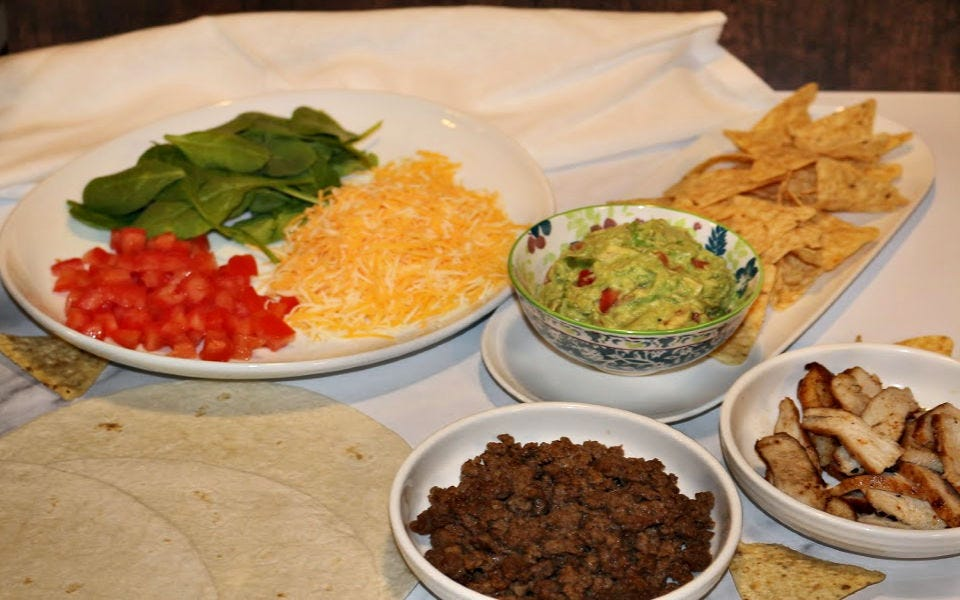 A quesadilla bar with toppings, ground beef, grilled chicken, and chips with guacamole.
