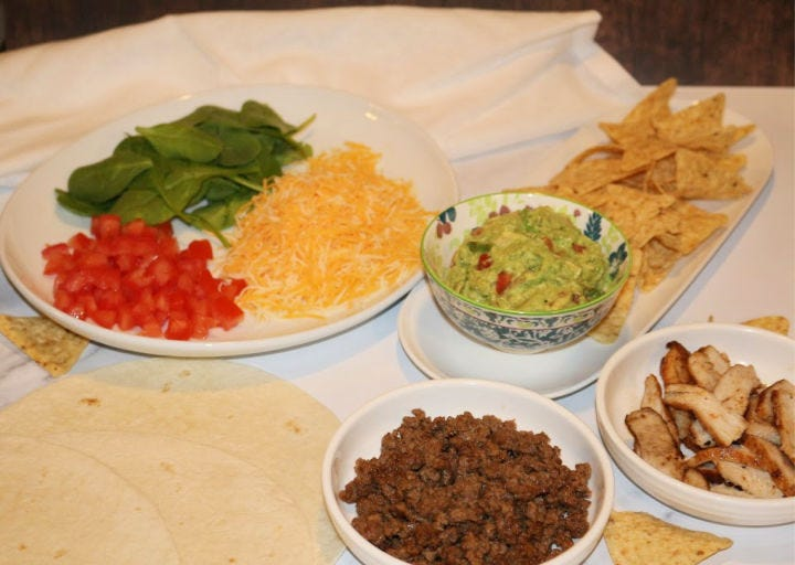 Arranged ingredients, including cheese, spinach, tomatoes, guacamole, chicken, and ground beef.