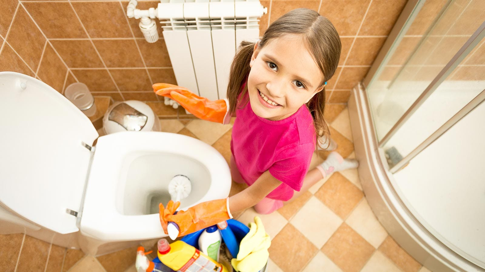 A little girl cleaning the toilet to help out with family chores.