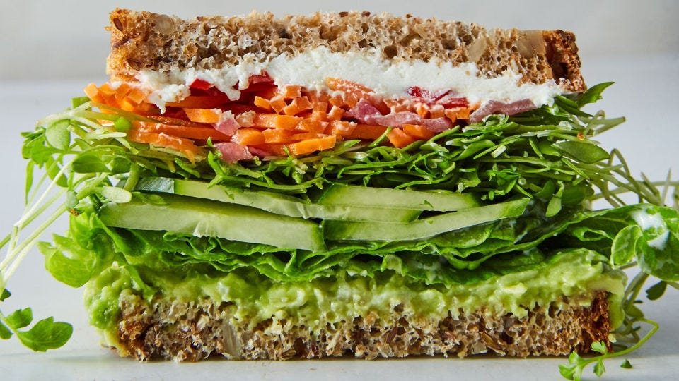 A California veggie sandwich piled high, stuffed with goat cheese, cucumbers, avocado sprouts, and homemade giardiniera.