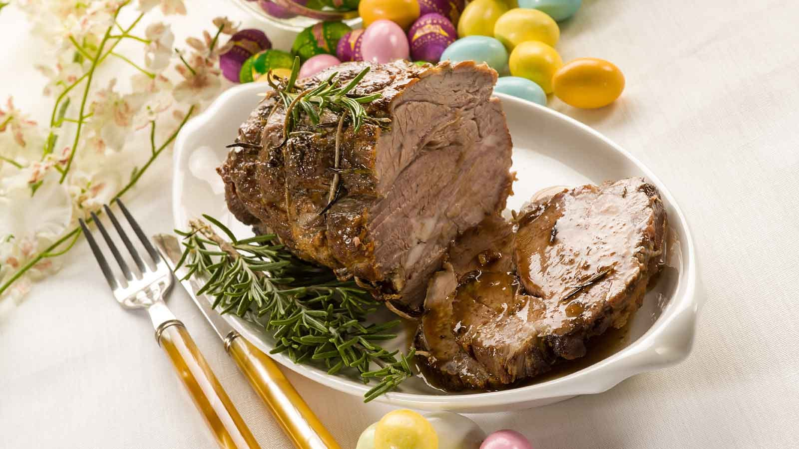 Sliced roasted lamb on a plate next to some colorful eggs.