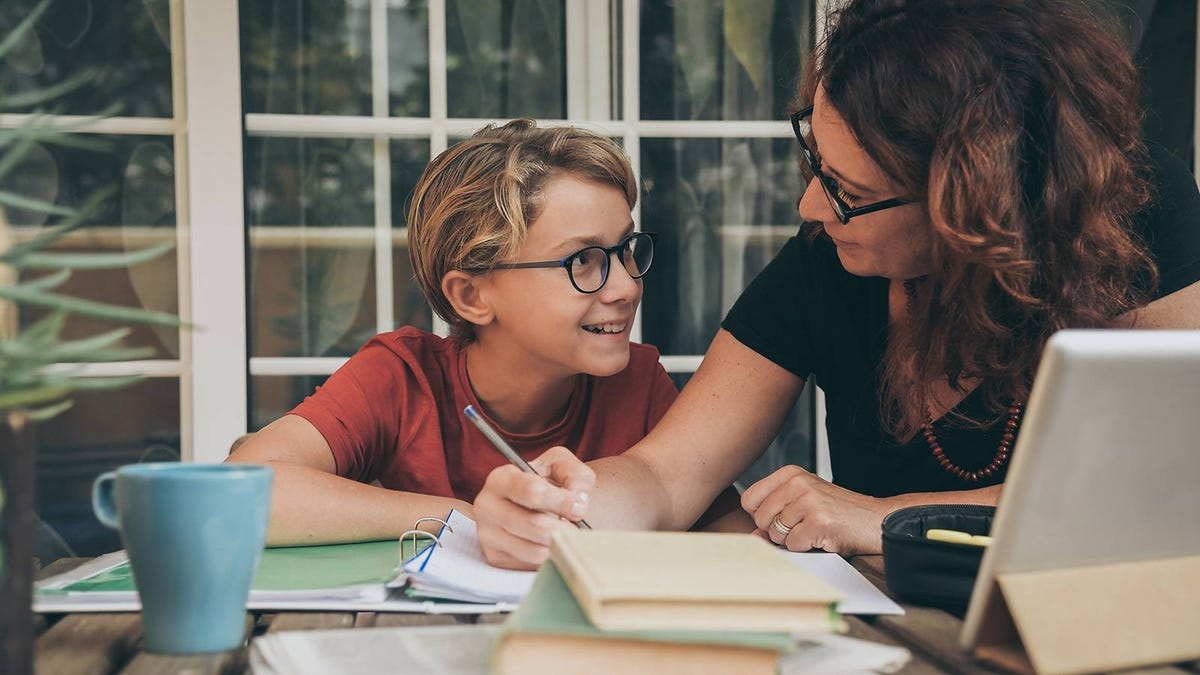 A mom working at the dining room table to create a schedule with her young son.