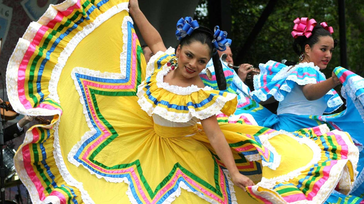 Dancers at a Cinco de Mayo celebration wearing traditional Mexican dresses.