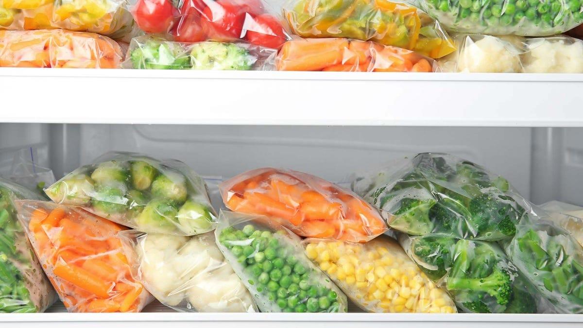 Ziploc bags full of veggies in a refrigerator.