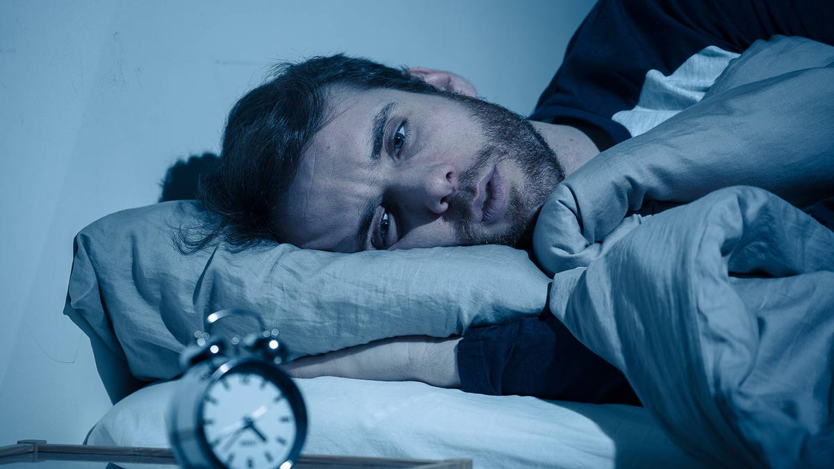 A man laying in bed, kept awake by anxiety.