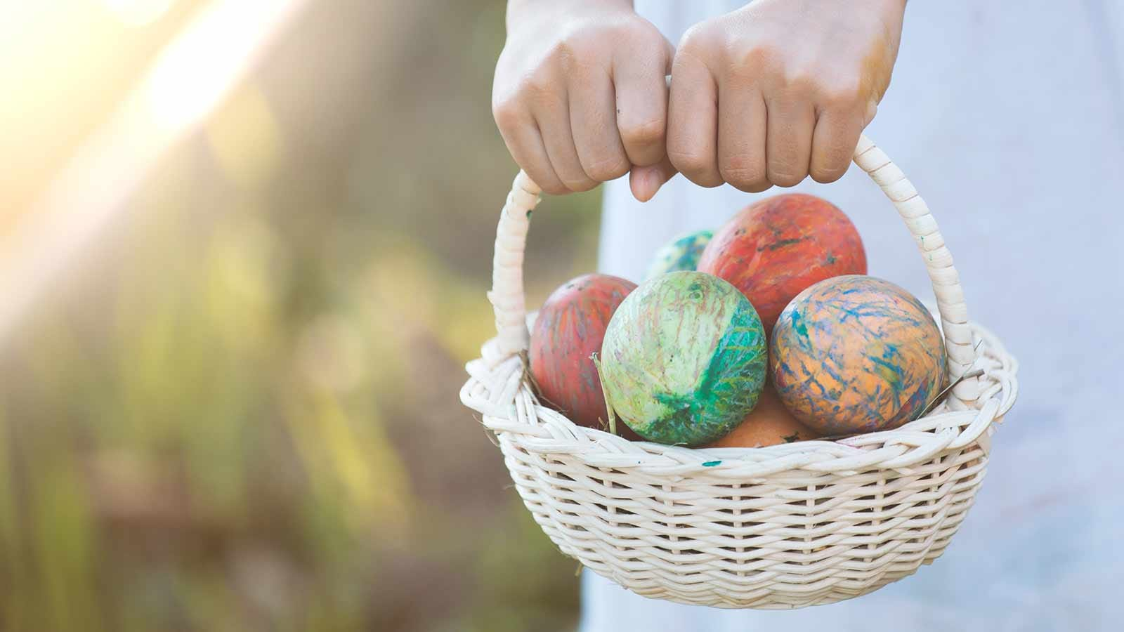 Hands holding a white basket of dyed Easter eggs.