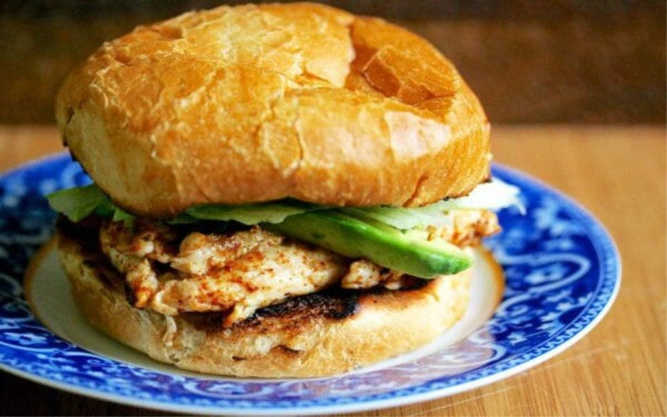 A grilled chicken sandwich with avocado and lettuce, on a blue and white plate.