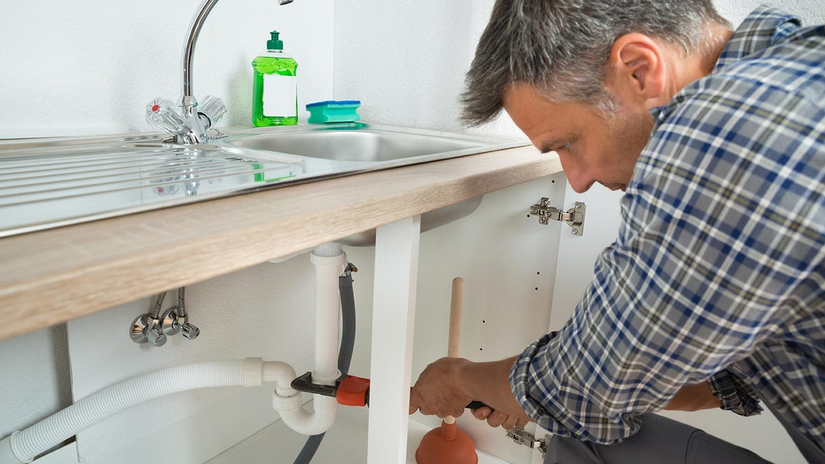 Man fixing sink drain with a wrench.