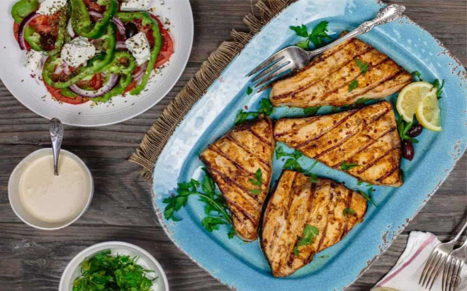 Swordfish steaks grilled to perfection, plated on a blue platter with a side of peppers, onion, tomatoes and feta cheese.
