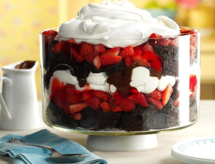 A layered trifle, filled with chocolate cake, strawberries, cool whip and frosting.