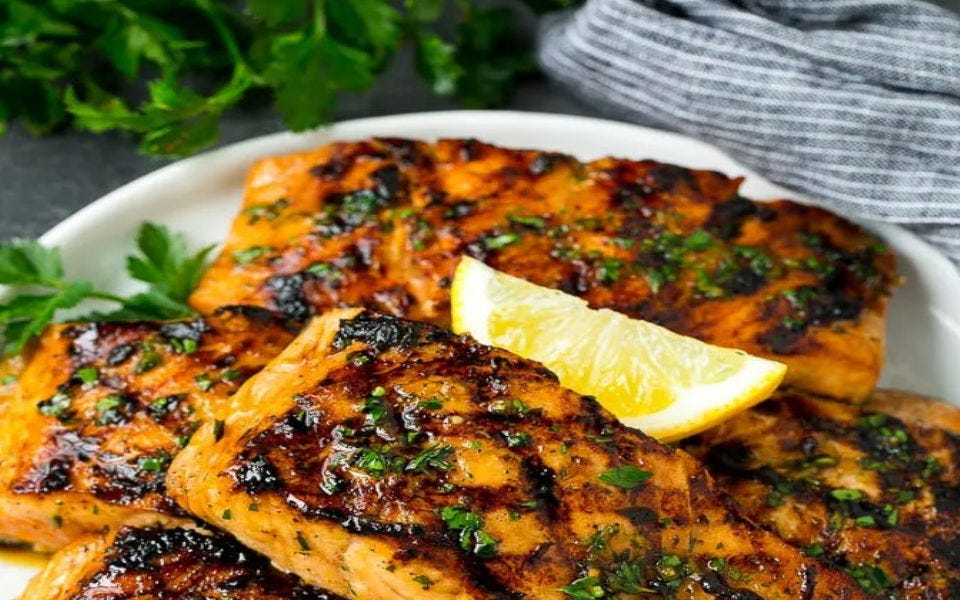 Freshly grilled salmon topped with a slice of lemon.
