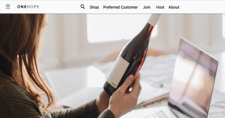 The One Hope Wine club website showing a woman holding a bottle of wine.