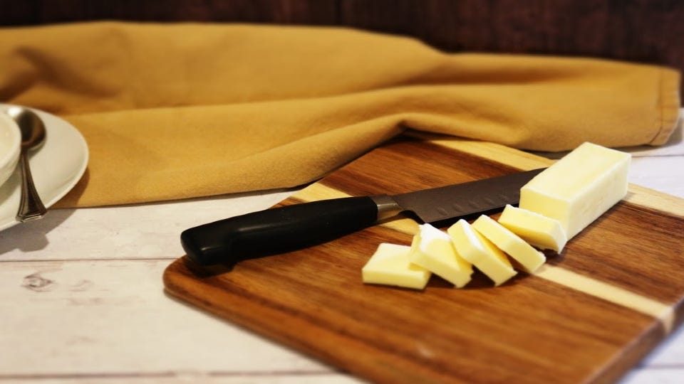 A stick of butter, cut into small pieces on a cutting board.