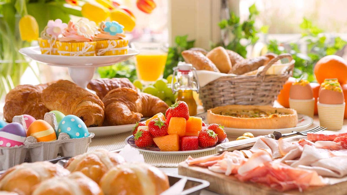 An Easter brunch table laid out with piles of traditional foods like fresh fruits, eggs, and meats.