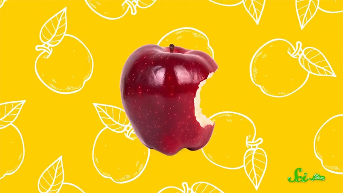 An apple with a bite taken out of it, against a background of fruit drawings.
