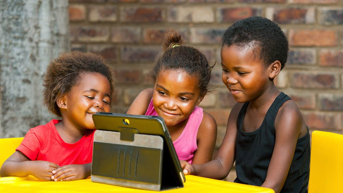 Three children gathered around a table watching an educational video on a tablet.