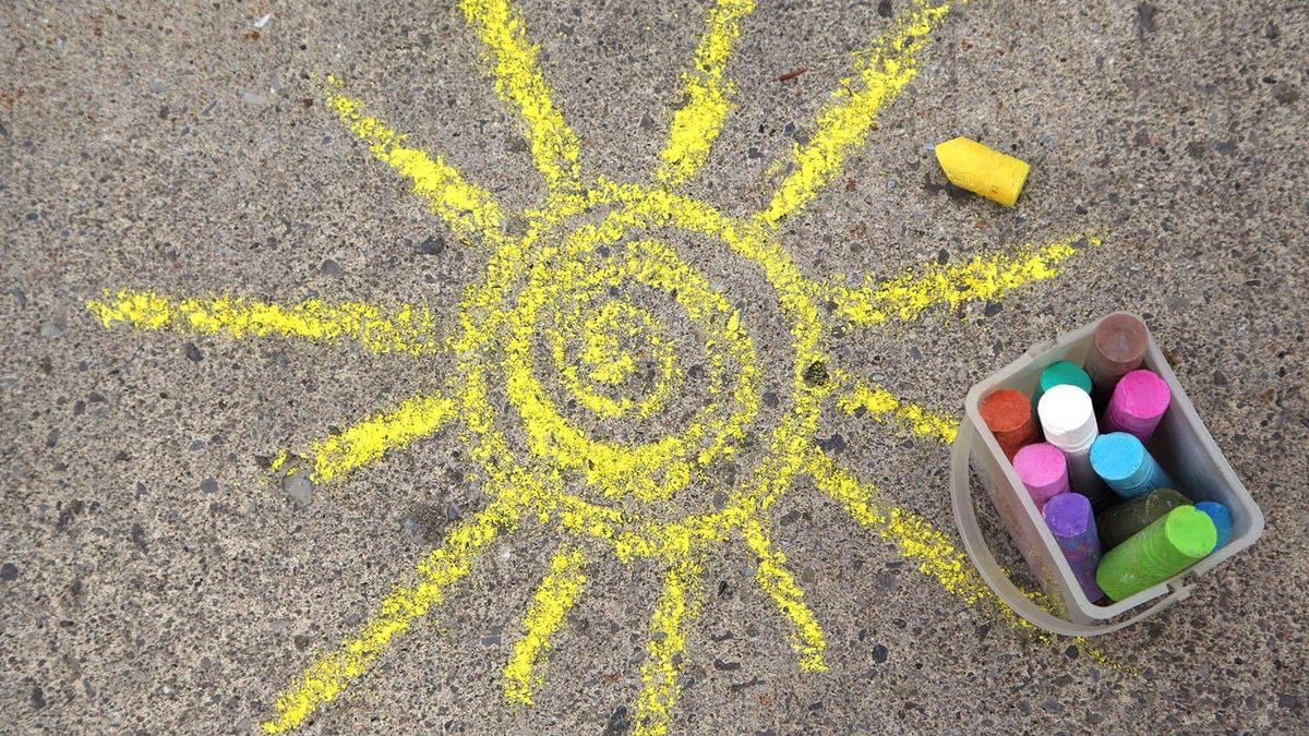 A chalk drawing of a bright yellow sun on pavement.