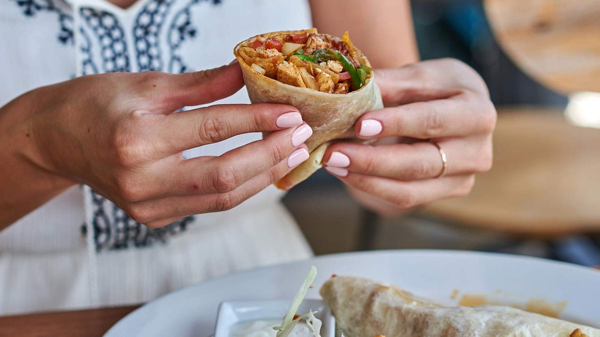 Female hands holding a burrito.