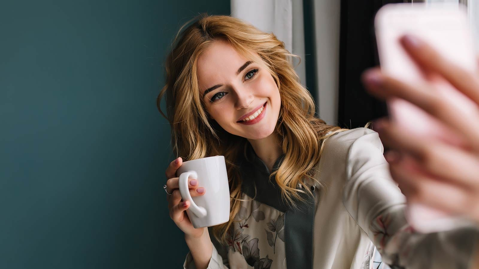 A young woman holding a coffee mug and taking a selfie with her phone.