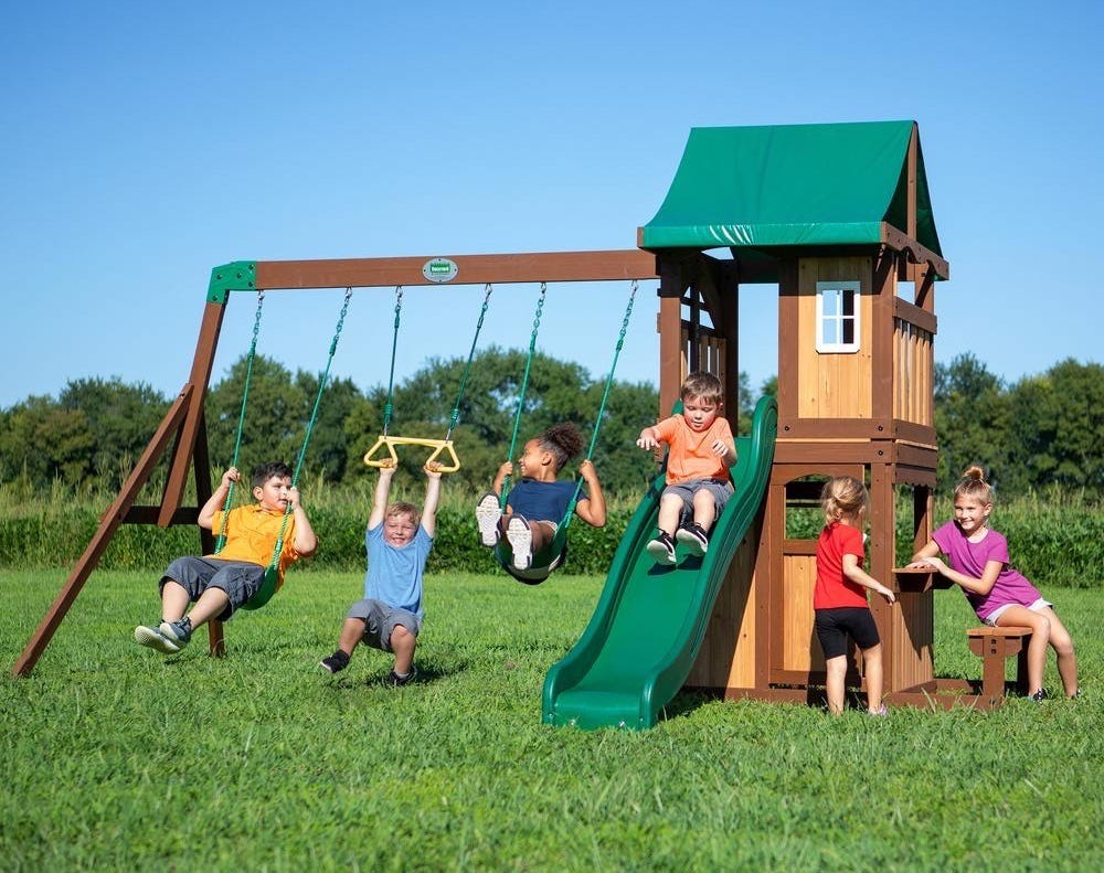Six children playing on the Lakewood wooden Swing Set's two swings, trapeze rings, slide, and clubhouse.
