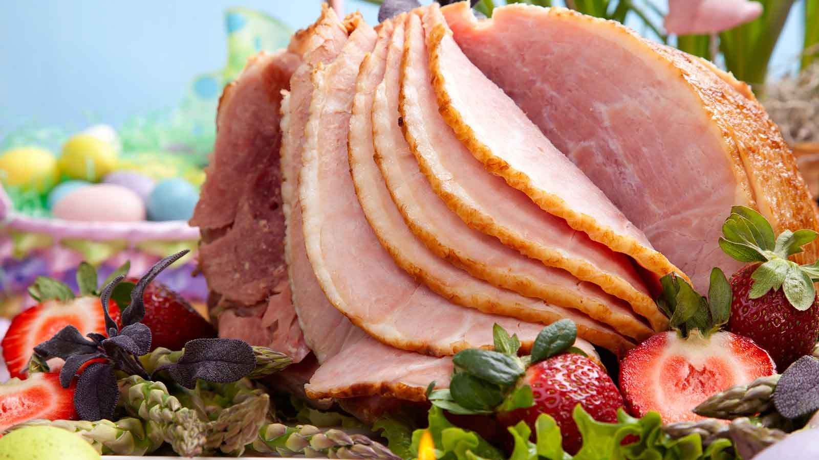 A sliced baked ham fanned open on a bed of fruit next to some colorful Easter eggs.
