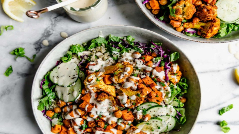 Two gorgeous shawarma bowls filled with chickpeas, sweet potatoes, cucumber.
