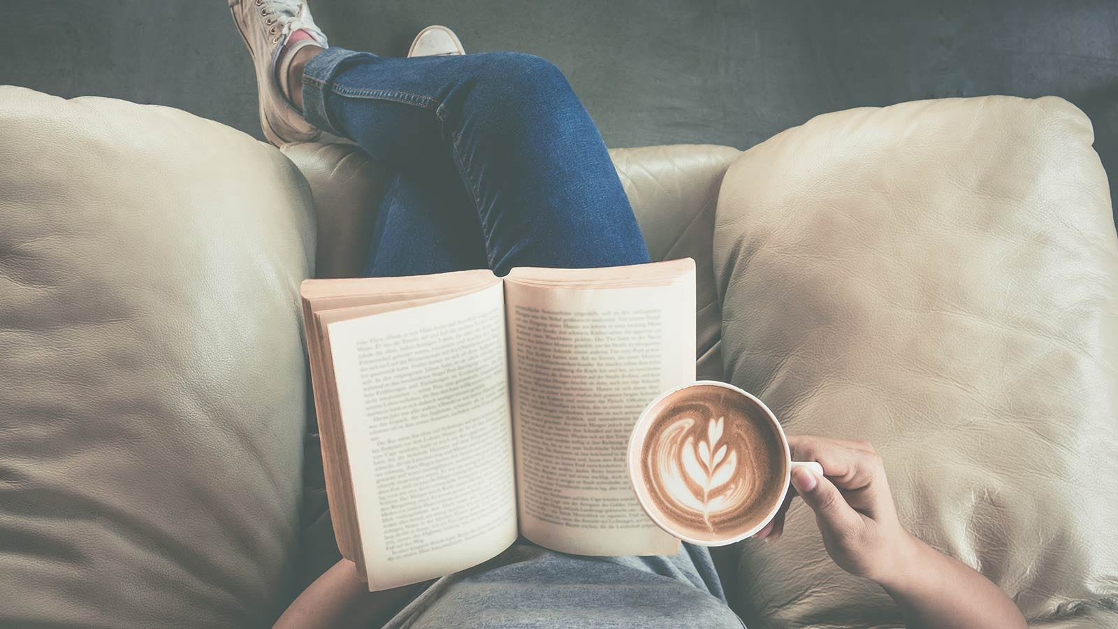 A woman's hand holding a mug of coffee with an open book in her lap.