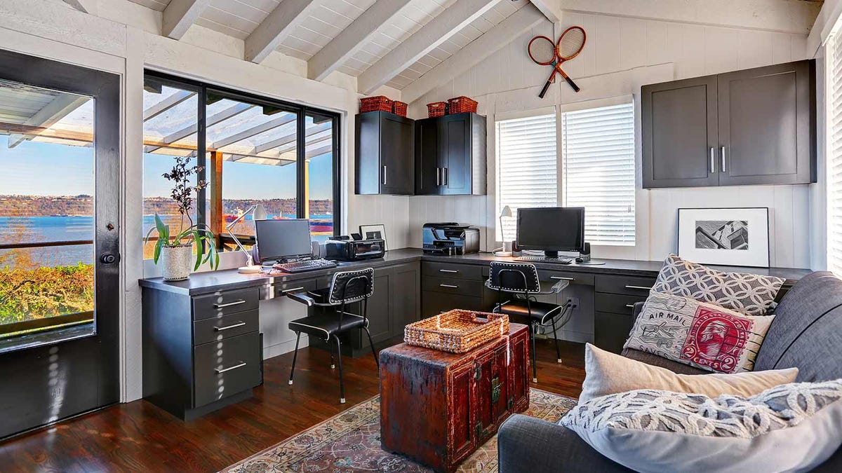 A tidy home office with a beautiful view of a bay out the windows.