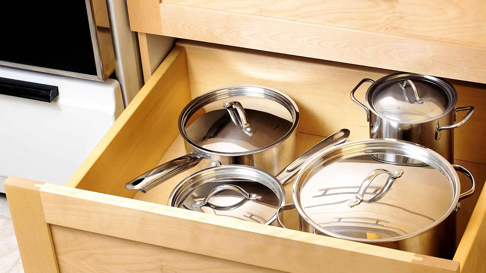 An organized kitchen drawer with tidy pots and pans.