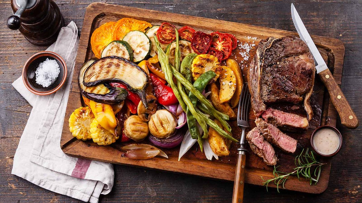 A cutting board loaded with a freshly grilled steak and grilled vegetables.