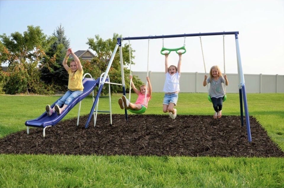 Four kids playing on a Great Outdoors Swing Set.