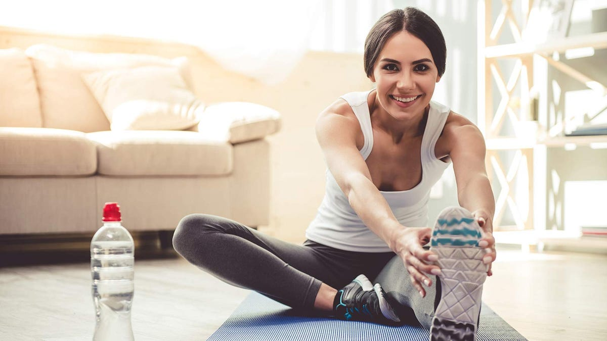 Woman stretching at home, preparing to lift some DIY weights.