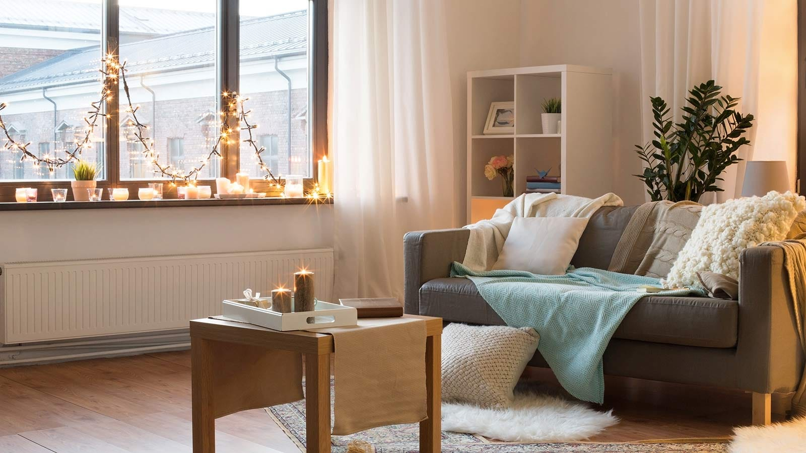 A living room with a window decorated with candles and Christmas lights.