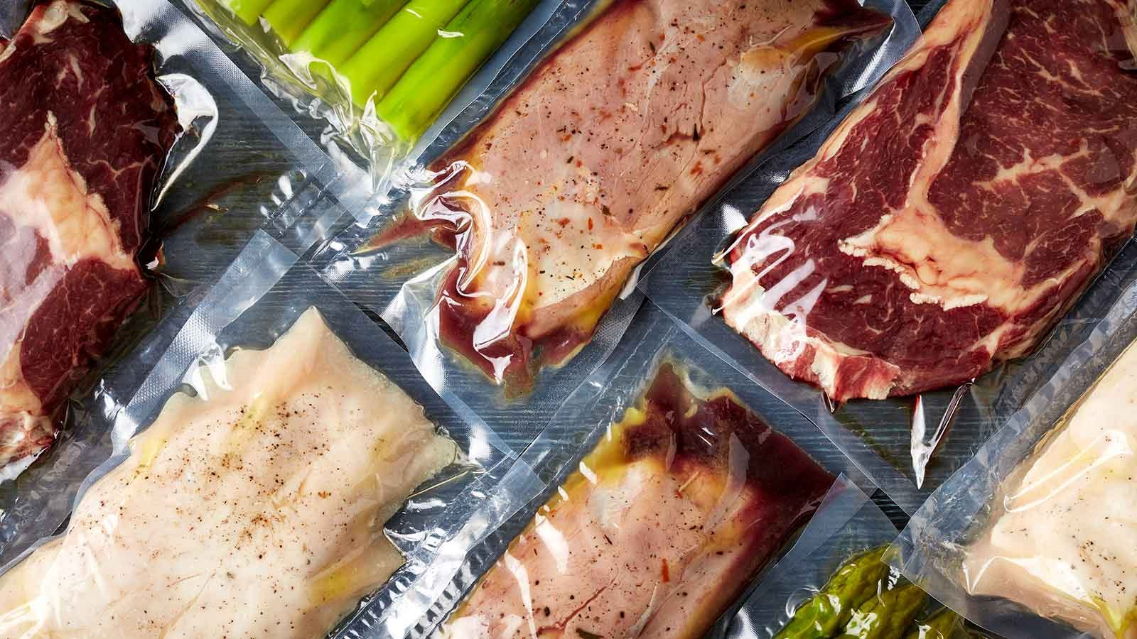 Vacuum sealed meats and vegetables laid out on a counter.