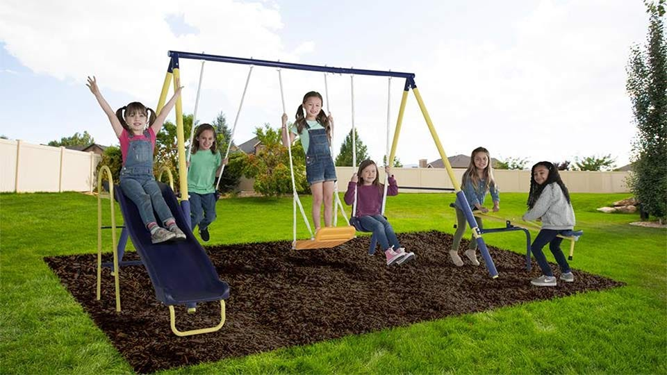 Six girls playing on the Sportspower Palmview Swing Set slide, glider, swings, and teeter-totter.