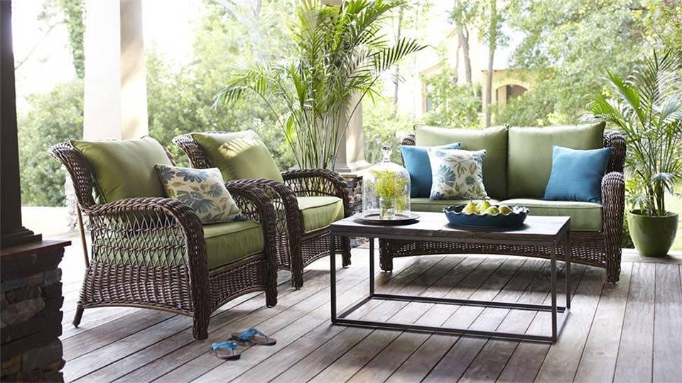 A set of outdoor wicker furniture arranged as a conversation set.