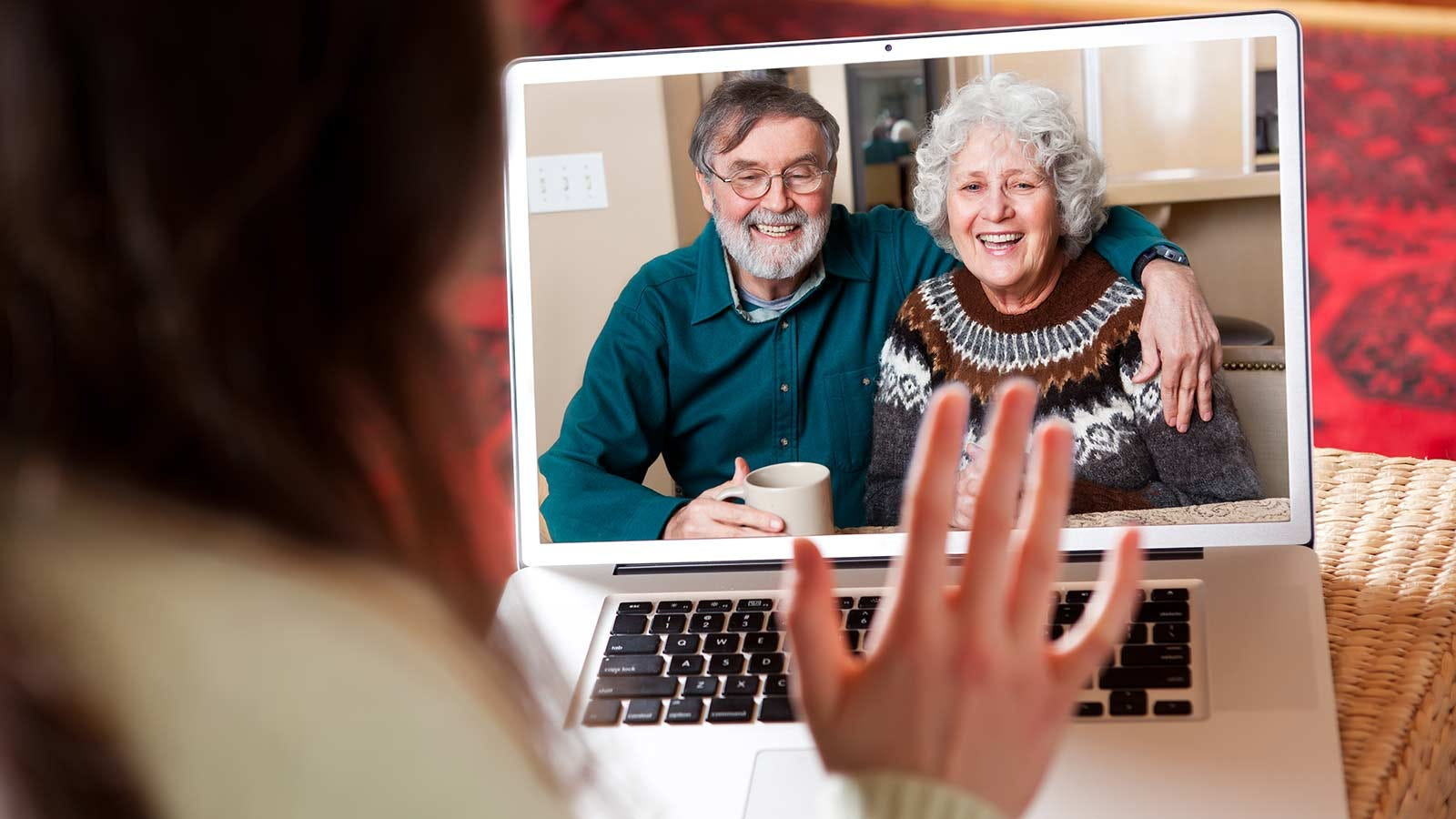 A woman's hand waving at an older man and woman on a laptop screen.
