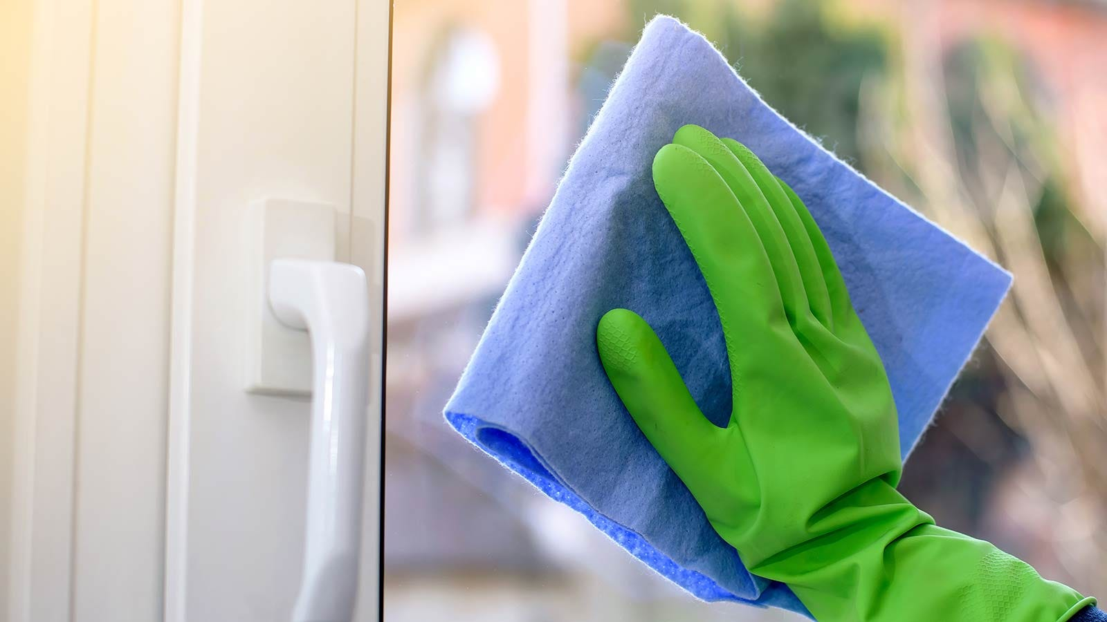 A gloved hand cleaning a glass door with a cloth.