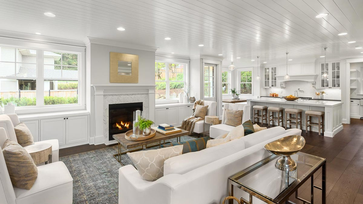An open floor plan connecting a living room, dining space, and kitchen.