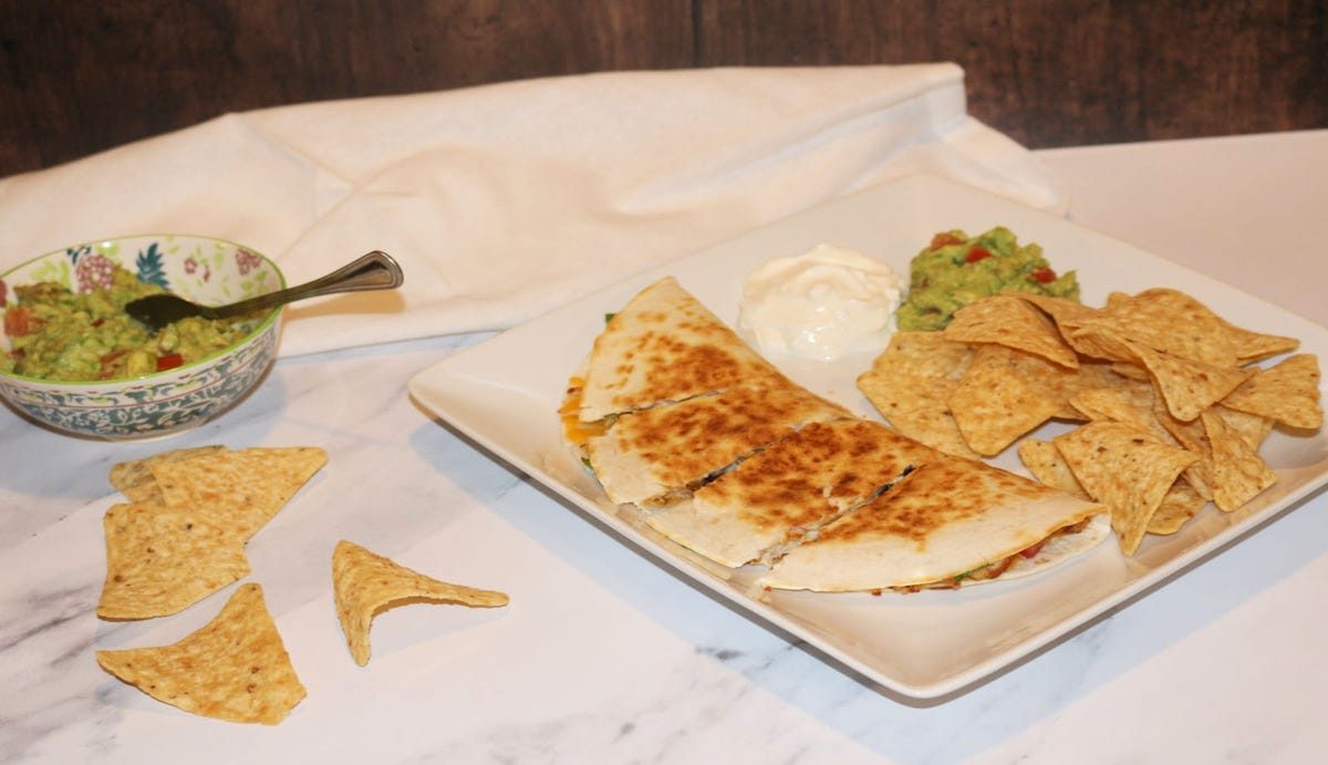 Fresh made quesadilla served with sour cream and guacamole next to a bowl of guacamole and scattered chips.