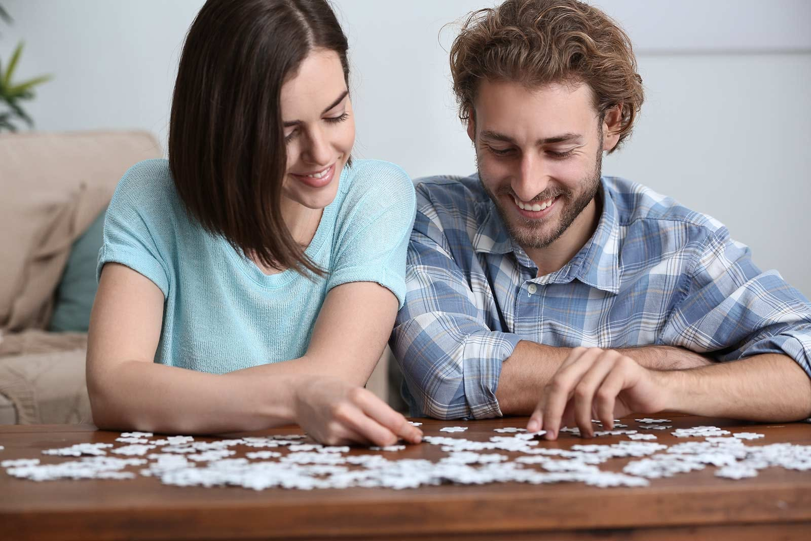 A man and woman working on a jigsaw puzzle.