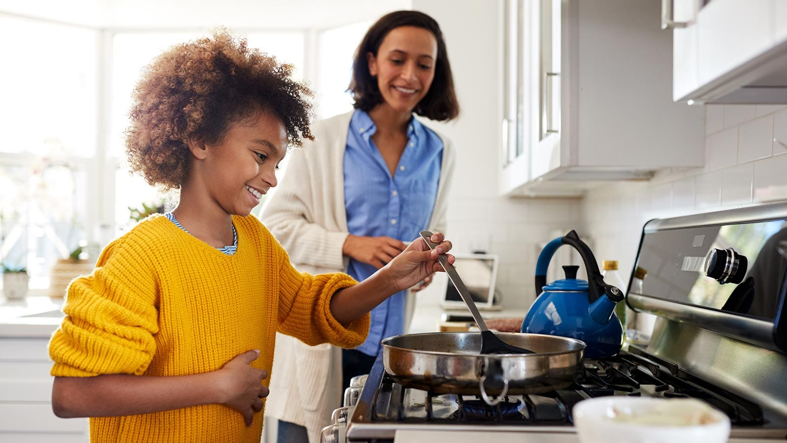 A mother supervises her daughter, as she cooks on the stove.