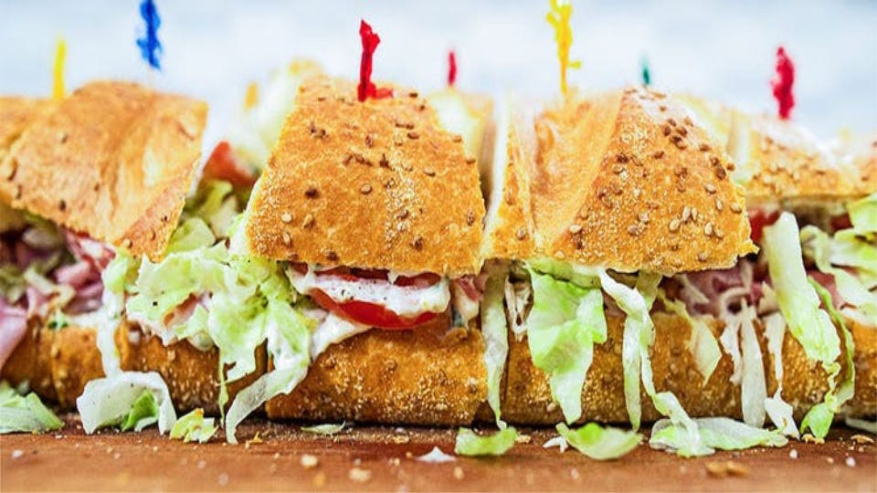 A stuffed submarine sandwich with club ingredients, including turkey, ham, lettuce, tomato, and herbed mayo.