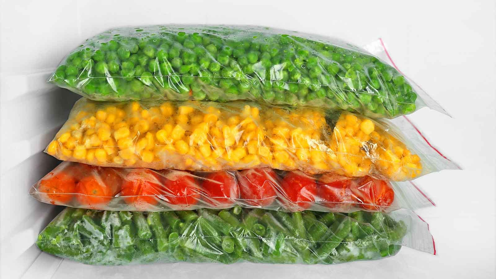 Stacked bags of frozen vegetables in a freezer.